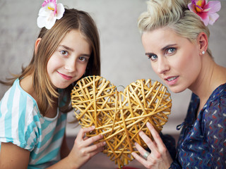 Mother and daughter keeping toy heart