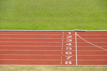 Start and finish line of red running track sports field.