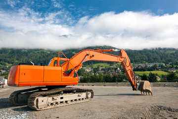 Excavator at construction site on austrian alps background