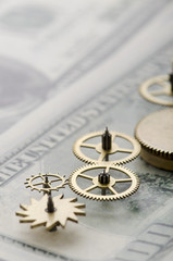 Gear wheels on dollar bill revealing the path to success