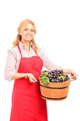 A female vintner holding a basket full of wine grapes