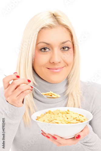 A blond female eating cornflakes at breakfast