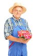 Mature gardener with panama hat holding a bunch of flowers