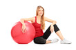 Young female athlete sitiing on a floor next to a pilates ball