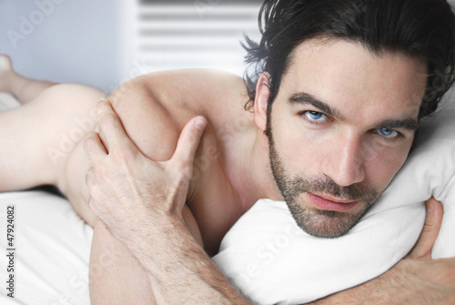 Portrait of a sexy nude man in bed