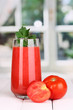 Glass of tomato juice on wooden table, on window background