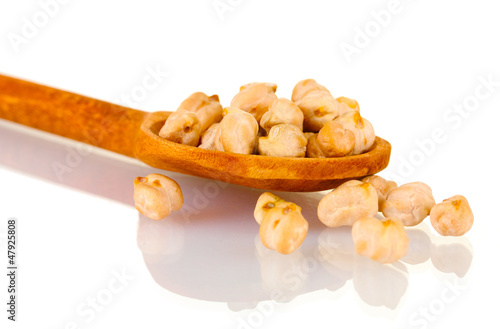 White chickpeas over wooden spoon isolated on white