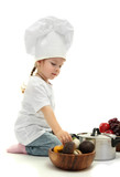 little girl doctor in chef's hat with pan and vegetables,