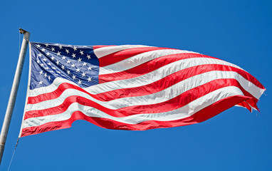 American Flag Flying in Bright Blue Sky