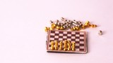Small chessmen by turns fall from chessboard on white background