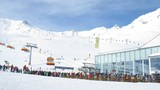 People wait near station of rope-way of queue in zone of skiing