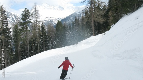 Tourists go on skis on piste, moving down
