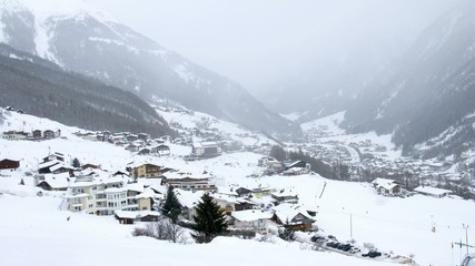 In valley where there are hotels and skiers it is snowing