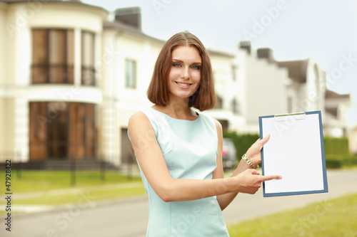 Female architect standing with folder near house