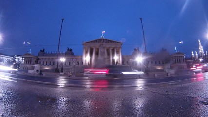 Cars go near to Viennese Parliament when it is raining