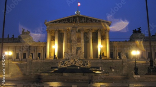Tourists walk near Austrian parliament in evening