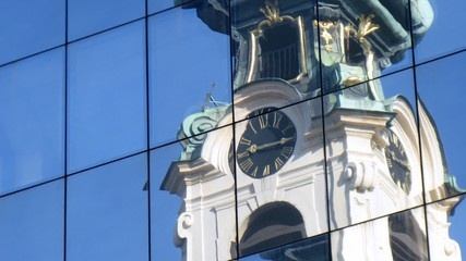 Clock in tower of monastery Stiftskirche are reflected in glass