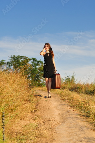 Lonely girl with suitcase at country road