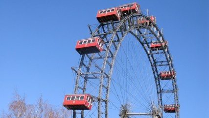 Big wheel rotates and stops against blue sky