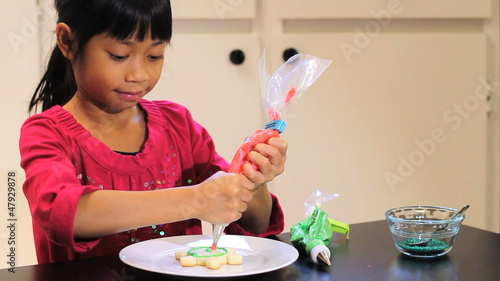 Asian Girl Adds Red Icing To Christmas Cookie