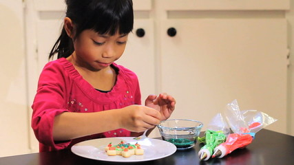 Asian Girl Adds Sprinkles To Christmas Cookie