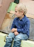 Kind sitzt auf Holzhaus