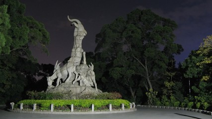 Tourists are photograph at left to Sculpture of Five Rams in