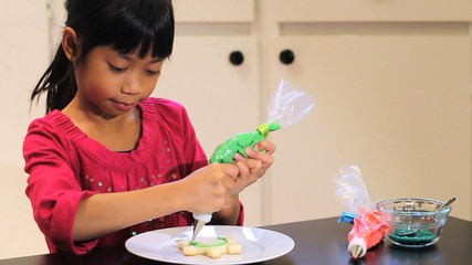 Cute Asian Girl Decorates Christmas Cookie