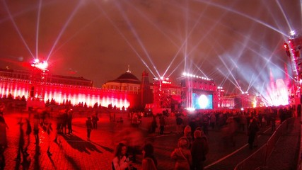 Many people stand and look laser show on Red Square festival