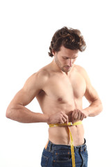 Sexy man measuring his waist with a measure tape