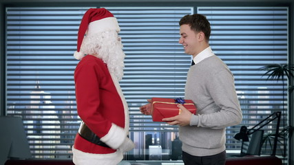 Businessman receiving a present from Santa Claus in an office