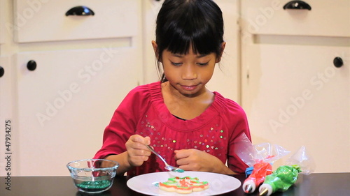 Girl Adds Sprinkles To Her Christmas Cookie