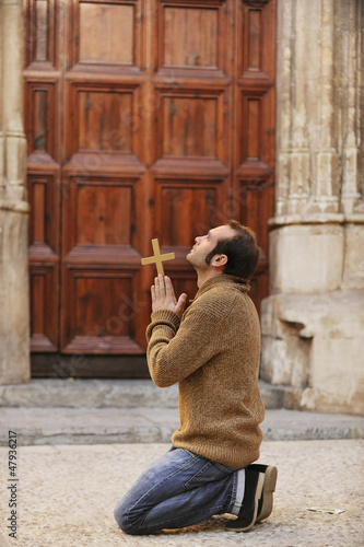 Man praying in front of the church holding a cross