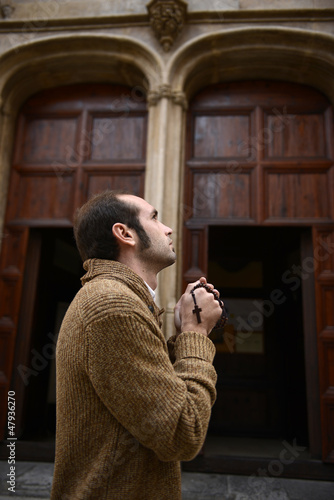 Man praying in church holding prayer beads