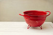 Red empty colander on white wooden table