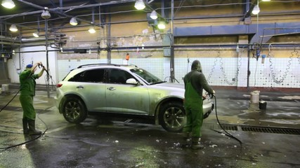 workers of car washing water car with streams of water from