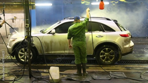 Two workers wash car indoors strong streams of water