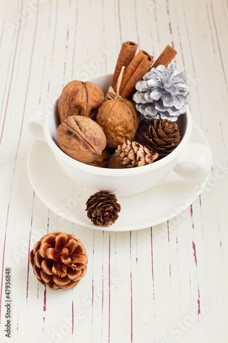 Walnuts and Christmas decor in cup on white tabletop