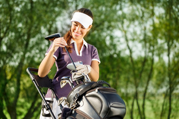 Young brunette woman with golf equipment