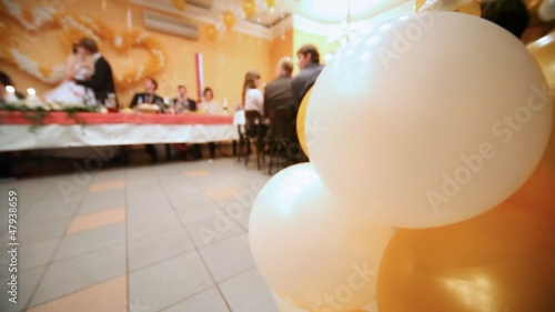 Close up balloons, behind newly-married couple kiss standing up