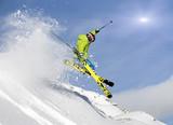 Młody narciarz skacze w głębokim śniegu