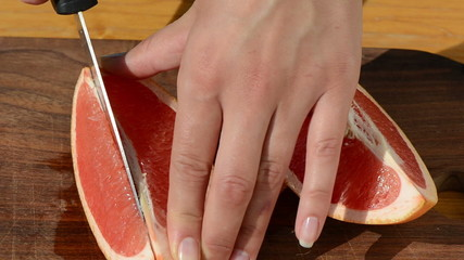 hand slice fresh ripe juicy grapefruit pomelo fruit into pieces