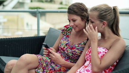 Young female friends with smartphone in the city