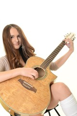 An attractive young teenage woman with an acoustic guitar