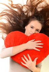 lovely woman with red heart-shaped pillow over white