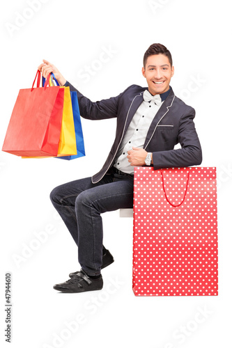 A smiling elegant guy posing with shopping bags in his hand