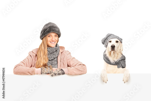 A smiling female posing with labrador retriever dog behind a pan