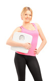 Blond smiling female athlete holding a weight scale