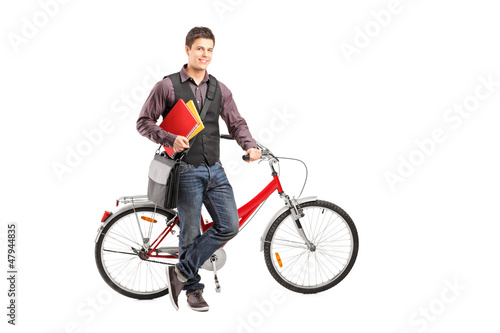 Smiling student holding books next to a bike