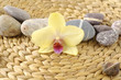 Pebble stones and yellow orchid on woven mat